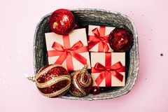 Silver box with presents and red christmas balls on pink pastel background. stock photo