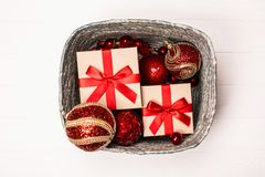 Silver box with presents and red christmas balls on white wooden background. royalty free stock images