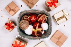 Silver box of red balls with round of presents on white wooden background. Silver box with presents and red balls surrounded by presents on white wooden royalty free stock photos