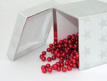 Silver box red beads. A silver gift box with red christmas beads hanging out Royalty Free Stock Images