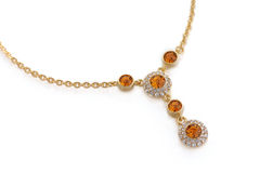 Silver bracelet. Gold necklace with orange and white diamonds Royalty Free Stock Images