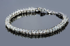 Silver bracelet with diamonds on gray background Royalty Free Stock Photo