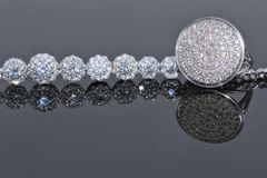 Silver bracelet with many sparkling diamonds and elegant ring wi. Th precious stones on a reflective surface Stock Image