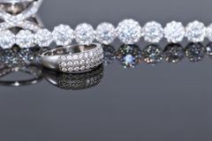 Silver bracelet with many sparkling diamonds and elegant ring wi. Th precious stones on a reflective surface Stock Images