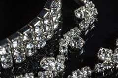 Silver bracelet and necklace with diamonds on black background close-up.  Stock Photos