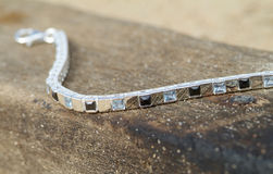 Silver bracelet on a piece of wood Royalty Free Stock Image
