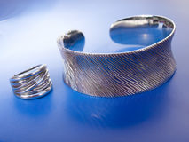 Silver bracelet and ring. In the blue background Stock Image