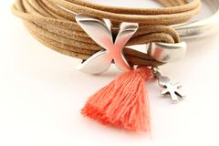 Silver bracelet with leather cord and orange pompon. Silver bracelet with zamak beands, leather cord and orange pompon Stock Photo