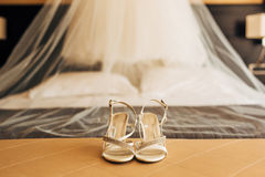 Silver Bride shoes on a bed before ceremony Stock Photography