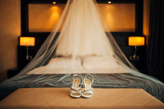 Silver Bride shoes on a bed before ceremony Stock Images