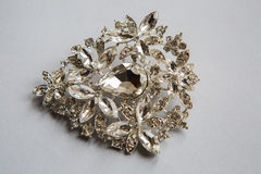 Silver brooch in the shape. Made of clear stones on a white background Royalty Free Stock Photo