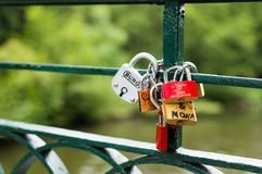Silver Brown and Red Padlock on Green Steel Trail Royalty Free Stock Photography