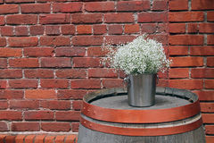 Silver Bucket of  Baby`s Breath Sitting on a Wine Barrel Stock Images