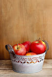 Silver bucket of red apples on wooden table. Stock Photos