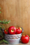Silver bucket of red apples on wooden table. Royalty Free Stock Images