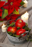 Silver bucket of red ripe apples among candles Stock Photos