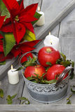 Silver bucket of red ripe apples among candles Royalty Free Stock Images