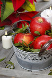 Silver bucket of red ripe apples among candles Stock Images