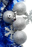 Silver bulbs with snowflakes and blue tinsel Royalty Free Stock Photography