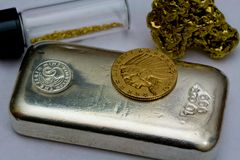 Silver Bullion Bar, Gold Coin and Gold Nuggets. 10 ounce silver bullion bar, $5 Indian Gold Coin and natural gold nuggets - Precious metals stock image
