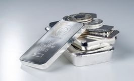 Silver bullion. Cast and minted bars and coins on a gray background. Selective focus stock photo