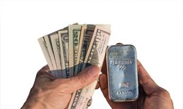 Silver bullion 1 kilo and dollar bills in the hands isolated on white royalty free stock photo