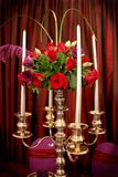 Silver Candelabra with Roses. Event décor, a bright, shiny silver candlestick with red roses, purple blooms and green foliage Stock Image