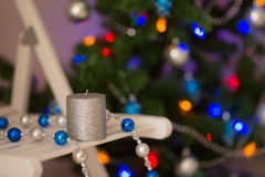 Silver candle on the background of the Christmas tree Royalty Free Stock Photo