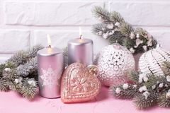 Silver candles, branches fur tree and balls on pink background. Against white wall. Place for text. Selective focus royalty free stock photography