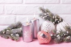Silver candles, branches fur tree and balls. On pink background against white wall. Place for text. Selective focus royalty free stock images