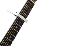 Silver capo on guitar fingerboard, white background Stock Photography
