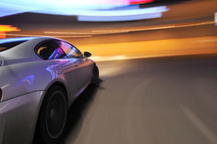 Silver car and blurry lights. Side view of modern silver motor car with colorful blurred lights background Royalty Free Stock Image