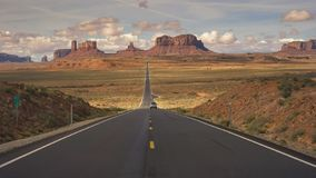 Silver car on highway 163 at monument valley. A silver car drives away from the camera on hwy 163 at monument valley in utah, usa stock photos