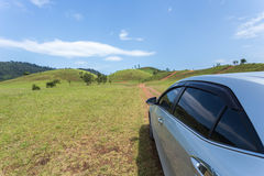 Silver car parking at the grass hill in Ranong province Royalty Free Stock Image