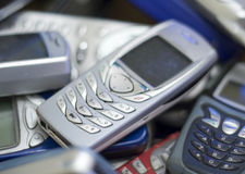 Silver cell phone in pile of others. A debadged mobile cell phone in a pile of other obsolete gadgets Royalty Free Stock Images