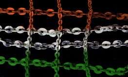 Silver chain in crisscross pattern painted orange and green. Closeup of bright silver chains arranged in a crisscross pattern on a black background. It is royalty free stock photos