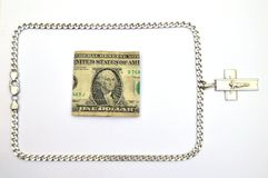Silver chain with crucifix and one dollar bill Royalty Free Stock Images