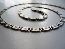 Silver chain on gray background. This photo shows a silver chain of test 925 on a gray background royalty free stock photos