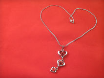 Silver chain lying in the form of heart Stock Photos