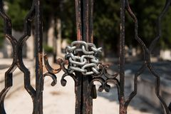 Silver chain on a metal graveyard fence. Closed old metal doors with metal chain. royalty free stock images