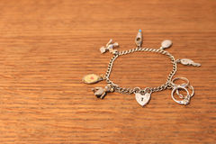 Silver charm bracelet on a scratched wooden background. Selective focus Royalty Free Stock Images