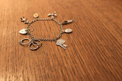 Silver charm bracelet on a scratched wooden background. Silver charm bracelet scratched wooden background (selective focus Stock Photography