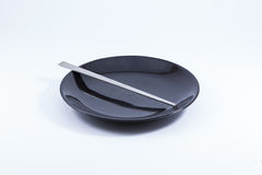 Silver chopsticks on black ceramic plate. ( on white bac Royalty Free Stock Images