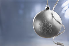 Silver Chrismast ball over blue background Royalty Free Stock Images