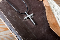 Silver Christian cross on bible Stock Photos