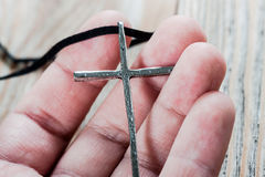 Silver christian cross in hand Royalty Free Stock Photography
