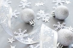 Silver Christmas background. Curly ribbon with decorative balls and snowflakes. royalty free stock photography