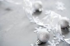 Silver Christmas background. Curly ribbon with decorative balls and snowflakes. Xmas decorations. Copy space stock photography