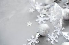 Silver Christmas background. Curly ribbon with decorative balls and snowflakes. Xmas decorations. Copy space royalty free stock image