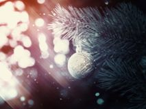 Silver Christmas Ball on a Branch. Decorative Christmas ball made of silver glitters on a spruce branch fantasy background Royalty Free Stock Photography